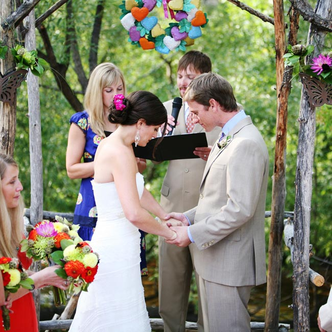 The ceremony took place near a creek on Darcie's family's property. Darcie's dad and Andrew built an arch from branches found on the land. Friends adorned the structure with a Mexican tin wreath of hearts that hung over the couple as they exchanged vows.
