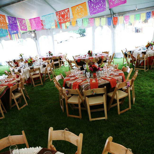 The couple kept the same whimsical fiesta feel for their reception tent, but brightened the space with papel picado (Mexican paper flags) and bright globe lanterns.