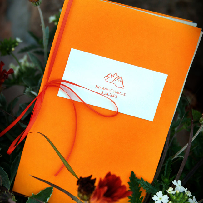 Charlie designed the program motif, the couple's names beneath a mountain silhouette. Kit tied the programs together with yellow, orange and cream ribbons and placed them on the guest chairs, along with stones to be used during a stone blessing ceremony.