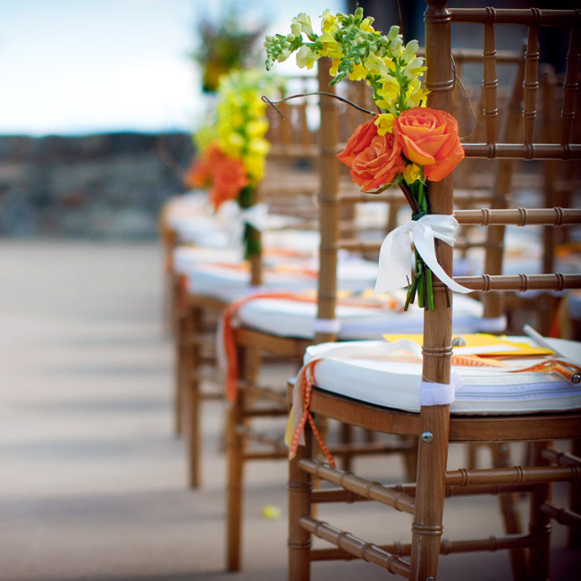 The couple complemented the natural décor of the ceremony site with urns of roses, freesias and snapdragons. They tied clusters of bright blooms to the ends of each row of chairs to mark the aisle.