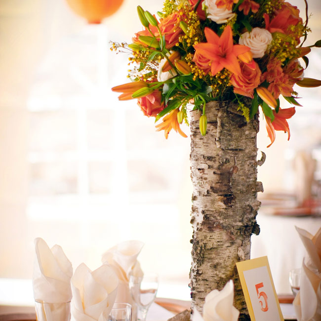 For an earthy touch to the decor, Charlie cut down sections of Aspen trunk from his family's ranch near Denver. Bright ranunculus, roses and freesia draped down the bark, while table numbers leaned up against it.