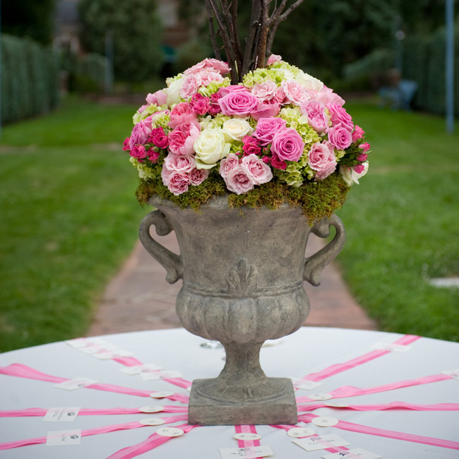 A large urn filled with pink and green blooms, moss and branches made for a stunning escort card display. Paper birds, resembling those on the invitation, hung from the branches, appearing to fly over the similarly designed guest cards below.