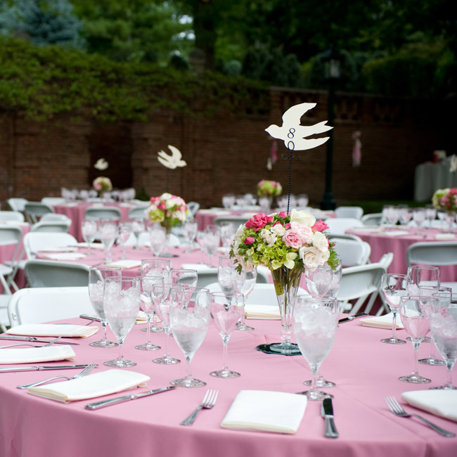 Pink linens and white napkins were placed around glass tripod vases filled with roses, ranunculus and geranium leaves for a simple, garden-party look.