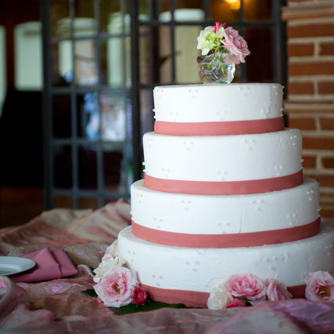Susan incorporated the same floral design of her bouquet into the cake topper. A glass bird vase displayed the fresh flowers atop the four-tiered dessert.