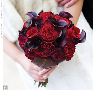 "Suzanne's only requirement for the flowers was that they be ""very red."" Her designer accommodated with Black Magic, Baccara and Wanted roses. Chocolate cosmos and eggplant calla lilies broke up the color with deeper tones."