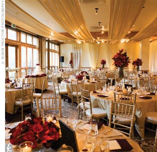 The elegant draping across the ceiling and down the walls was the bride's favorite part of the decor. The lush fabric perfectly complemented the champagne-colored linens, which were topped with eggplant napkins and surrounded by gold chiavari chairs.