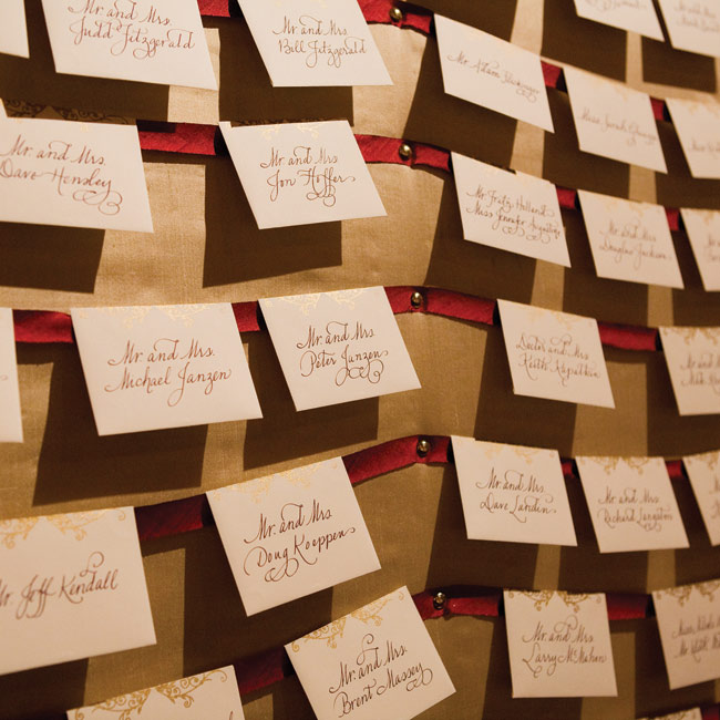 The couple transformed a giant hutch in the entry of the lodge ballroom into an escort card display. They camouflaged it with large sheets of plywood wrapped in cotton batting and champagne dupioni silk and hung the cards from strips of scarlet ribbon.