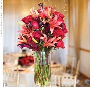 Earthy touches of pinecones and curly willow gave the elegant centerpieces of roses, calla lilies, cosmos and dahlias a rustic vibe. High and low arrangements added texture to the room.
