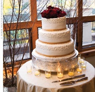 The couple's ivory, buttercream cake was kept simple, but still incorporated personal accents -- including the couple's signature wrought iron scroll and a topper made of fresh red roses.