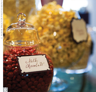 Old-fashioned candy dishes added vintage flair to the candy bar the couple set up for their guests. They offered a variety of popcorn and sweets, and provided monogrammed bags so each guest could take home some treats.