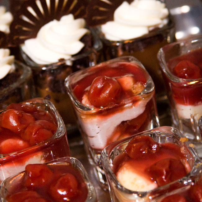 Miniature desserts in shot glass topped with cherries and chocolate fans complemented the cake.