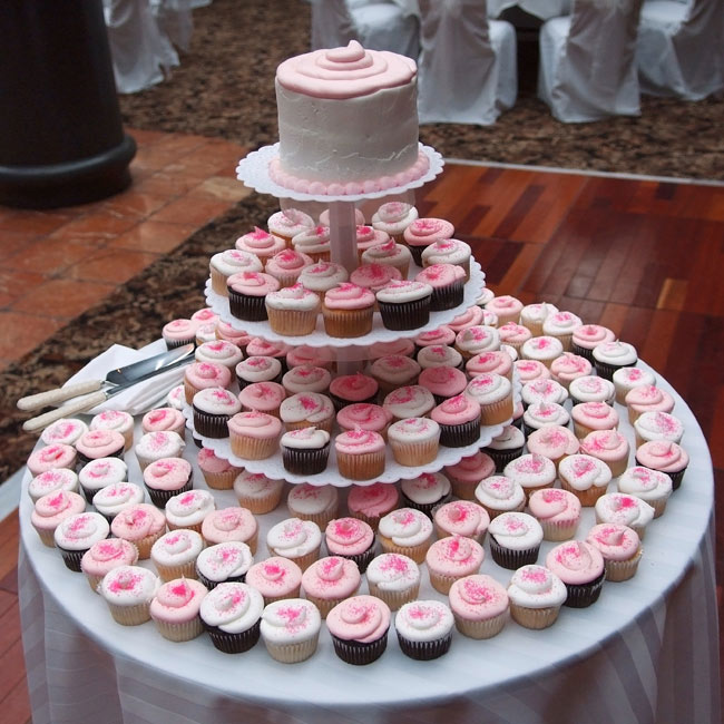 White, dark chocolate, and cherry cupcakes frosted with pink icing and sprinkles lined a cupcake tower.