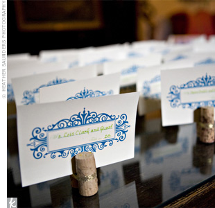 The bride and her family made the escort cards by tying together two wine corks with gold ribbon and placing cards printed with a scrollwork pattern between them.