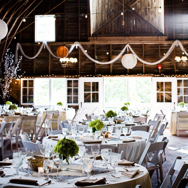 Large paper lanterns hung from the barn ceilings, while burlap runners dressed down white tablecloths.