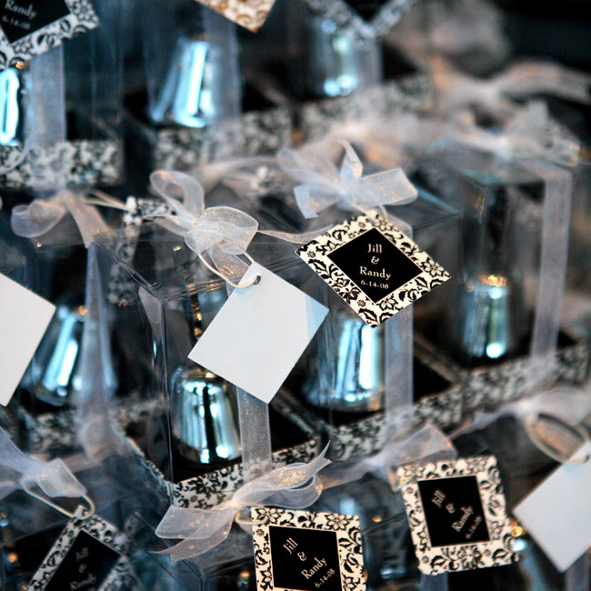 Gift tags with the couple's names and wedding date printed in a modern motif tied together boxes of silver wedding bells.
