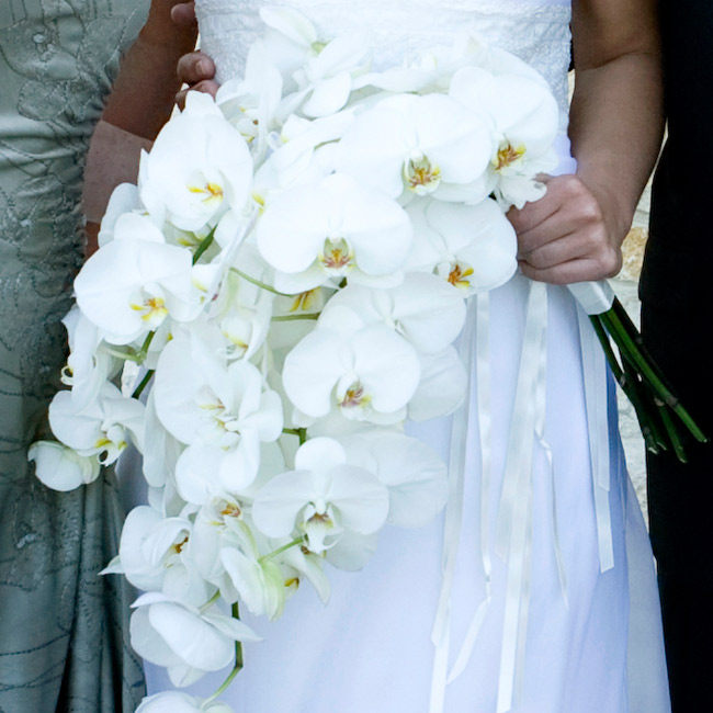 Georgina carried phalaenopsis orchids adorned with a jeweled three-leaf clover pendant, which she also added to her bridesmaids' bouquets.