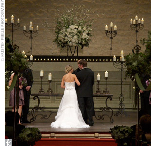 The couple exchanged traditional vows on a stage set with bronze candelabras and votive candles. Five-foot iron pew markers with green and ivory blooms ran along the aisle, leading to three altar arrangements with roses, hydrangeas and bells of Ireland.