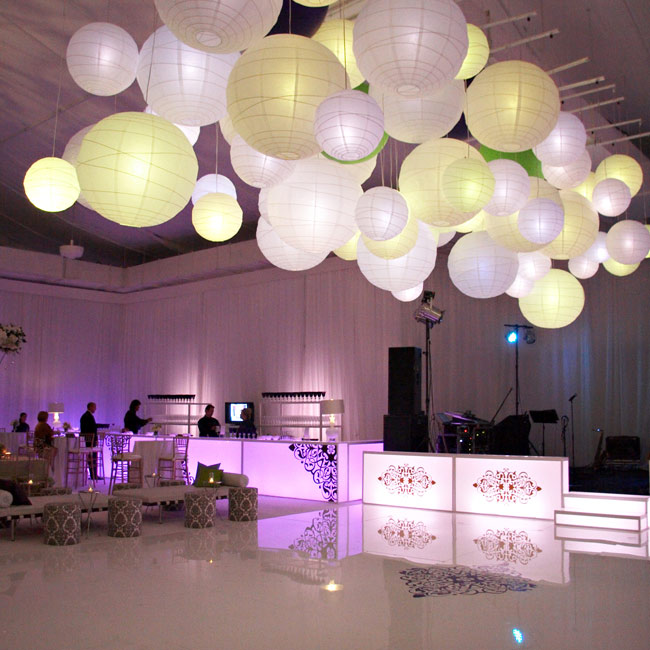 Fifty paper lanterns in assorted sizes hung above the dance floor. The soft shades of green and purple perfectly incorporated the couple's wedding colors without overwhelming the mostly-white décor.