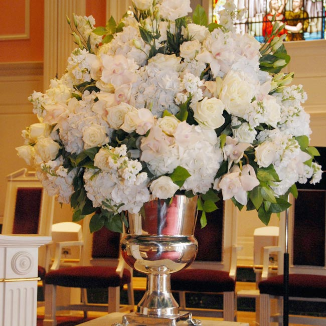 Simple clusters of roses with dangling ribbons hung from each pew, but the two altar arrangements of roses and hydrangeas in silver urns stole the show.