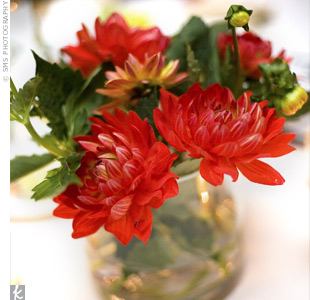 Yellow ranunculus and different shades of red dahlias decorated each table.