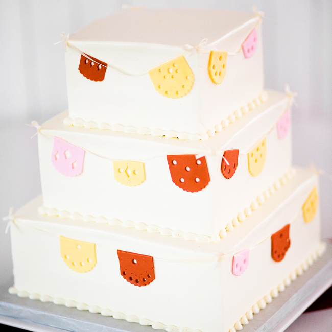 Melissa originally saw the cake of her dreams in a magazine and ran to her baker to see if she could make it. The finished product: A square cake with buttercream frosted tiers with fondant papel picado (Mexican craft of shapes cut into paper).