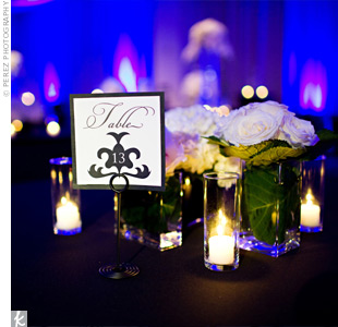 Modern table numbers with a monogram designed by the bride showed guests where to sit. Votives surrounded each table number to make it stand out (and easier to read!).