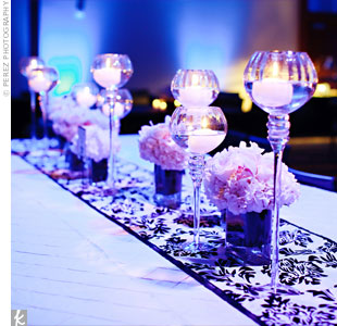 Votives in varying heights and square arrangements of hydrangeas and other colorful blooms sat on top of a patterned table runner that helped inspire the monogram design.