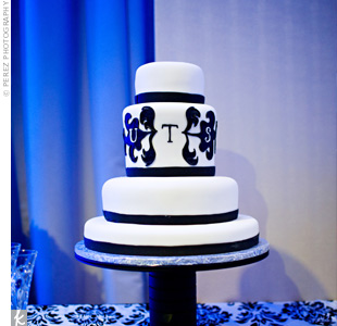 Black ribbon and an edible version of the couple&#39;s monogram decorated the four-tiered, fondant cake.