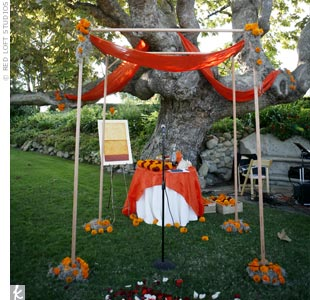The couple combined Laurie's Jewish faith and Anil's Hindu beliefs by creating a combination huppah-mandap. The structure was adorned with bright orange Indian silk, marigolds, and Spanish moss.