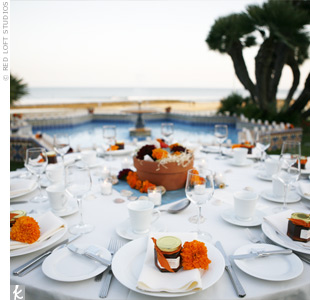 The reception tables were decorated with square, blue-green silk overlays and scattered with shells to reflect the oceanside setting. Blue, green, and orange flowers echoed the site's Spanish tiling.
