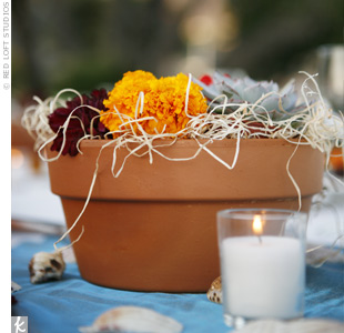 Bright centerpieces made of succulents and marigolds were displayed in terra-cotta pots topped each table.