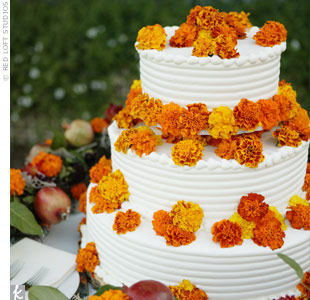 The couple opted for a three-tiered, organic blood orange cake. It was decorated with fresh marigolds and displayed on a bed of flowers and Spanish moss.