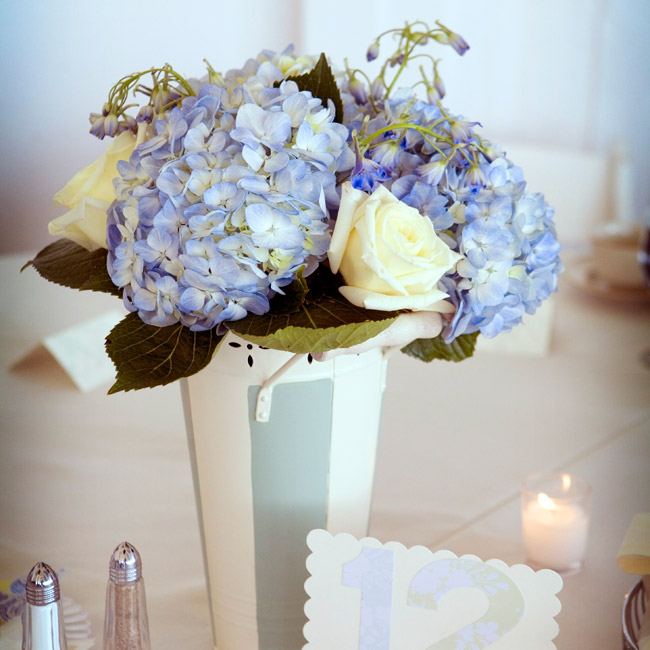 Painted galvanized buckets, which matched the painted ceiling of the room, held hydrangeas and creamy roses. Melissa made the table numbers with scrapbooking paper.