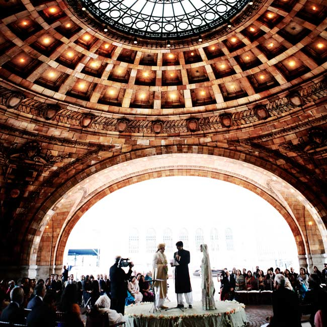 The traditional Muslim ceremony was held in the rotunda at the Pennsylvanian, just steps from the reception area. The couple made the space their own in several ways: They covered a custom-built stage in the same fabric used for the table linens, placed an oriental rug at the entrance to the ceremony space and brought in potted trees.