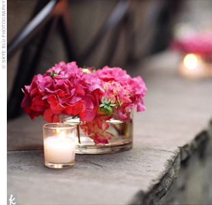Hot pink hydrangeas in small round vases and votive candles lining ledges added pops of color to the natural space.