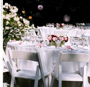 Clean white linens, napkins, and chairs accented with some pink rose centerpieces achieved a summer picnic vibe.