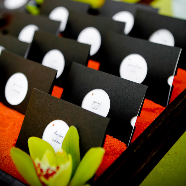 Designed to match the save-the-date cards, the white place cards were slipped into chocolate brown sleeves with cutout holes revealing each guest's name. The cards sat in brown boxes sprinkled with orange sand and green cymbidium orchids.