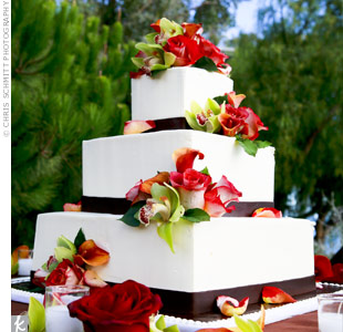 Green orchids and red calla lilies adorned the three-tiered, square cake, tying it into the rest of the reception décor.