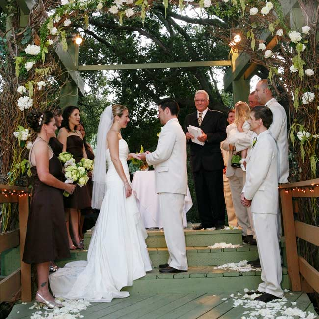 Casey and Clay exchanged vows in a simple outdoor ceremony under a trellis covered in vines and white flowers. As a personal touch, they performed a sand ceremony, where each holds a different container of sand and combines them into one vase to represent their new life as one