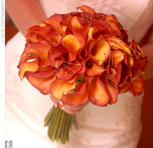 Golden-beaded flourishes sparkled in a bouquet of orange calla lilies.