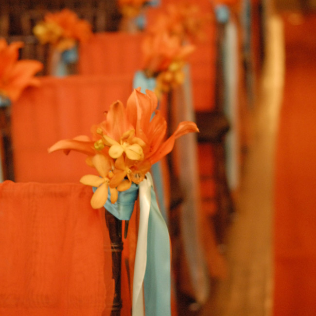 Orange lilies tied with cream and turquoise ribbon lined the ceremony aisle. Orange fabric draped over the backs of the chairs functioned as chair covers.