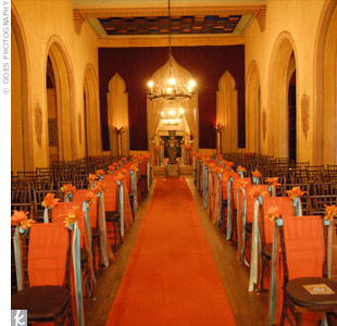 The Rabaat Room's tall ceilings and dramatic chandelier made it perfect for the ceremony. An orange aisle runner and floral chair ties added a touch of color.