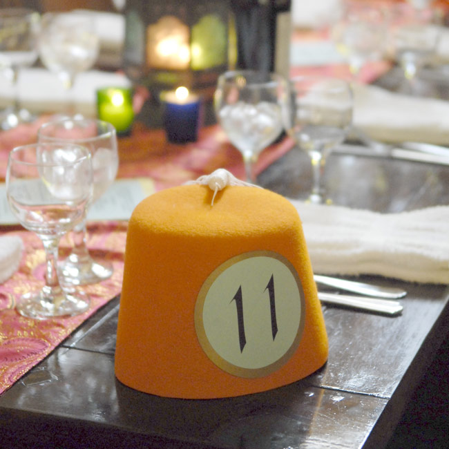 Sticking with the couple's colorful Moroccan theme, orange Fez hats printed with table numbers decorated the center of each table.