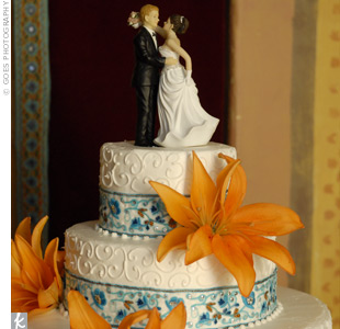 Inspired by a turquoise and orange ribbon the bride found in the fabric district in downtown L.A., the cake featured elaborate floral decor, white buttercream swirls and large orange blooms. A bride and groom topped the cake -- but they barely made it through the reception because the belly dancer knocked them down. The arms broke, but the wedding  ...