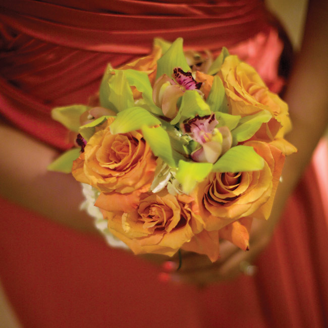 Angular, lime cymbidium orchids contrasted with round, orange roses for modern and vibrant bridesmaids' bouquets.