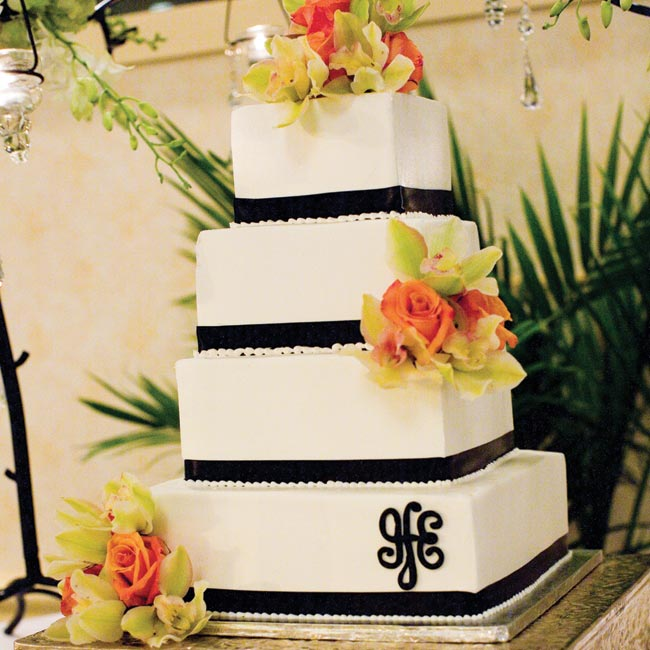 Instead of placing it at the top or in the middle, the couple's monogram decorated the bottom corner of the cake for a more modern approach. To work in the rest of the color scheme, clusters of roses and cymbidium orchids resembling the bridesmaids' bouquets made the tiers pop.