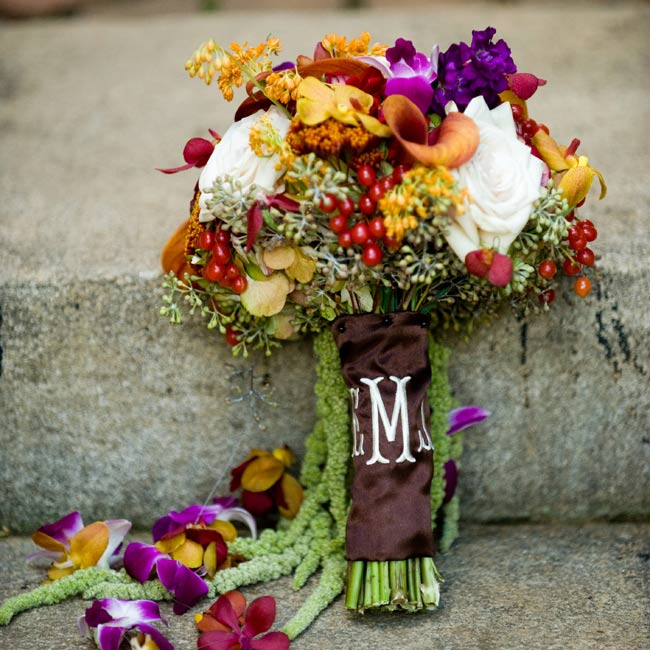 Hanging amaranthus and strings of orchids draped down from Elizabeth's bouquet. White roses and a monogrammed wrap further distinguished her arrangement from the bridesmaid bouquets.