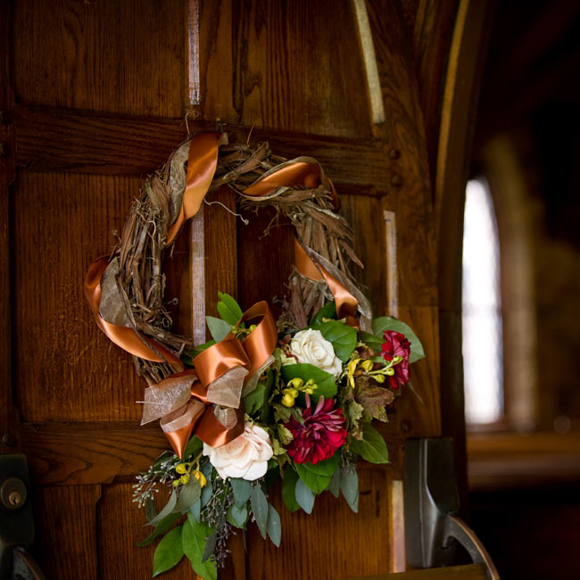 To put their personal stamp on their chapel of choice, the couple spruced up the doors with elaborate wreaths with copper ribbon woven in with the branches. An asymmetric cluster of flowers and greenery put a modern spin on the traditional decoration.