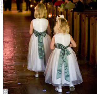 As they tossed petals from antique, silver baskets, Elizabeth's cousin and Scott's niece made their way down the aisle. The sage, satin sashes coordinated with the bridesmaids' gowns.