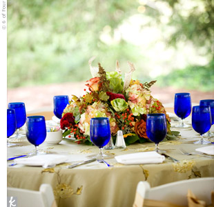 A textural mix of hydrangeas, roses and berries seemed to pour out onto the floral linens. Cobalt glassware contrasted with the predominantly green and blush arrangements.